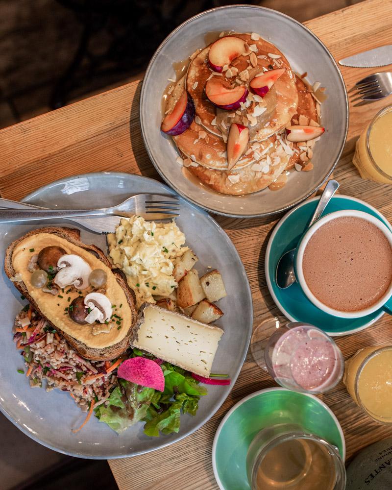 pancakes avec des fruits, du pain avec des œufs brouillés et un chocolat chaud