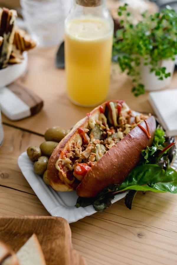 le hot dog de Coney Cookies classique avec une moutarde au miel, du ketchup, des cornichons, des oignons frits et une saucisse artisanale, le tout dans un pain brioché